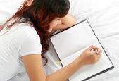 Girl writing book on the bed — Stockfoto