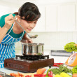 Woman is tasting her cooking — Stock Photo