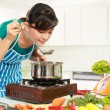 Woman is tasting her cooking - Stock Photo