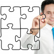 Businessman drawing puzzle — Stock Photo