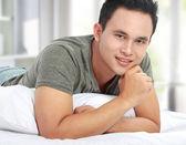 Hombre acostado en cama sonriendo — Foto de Stock