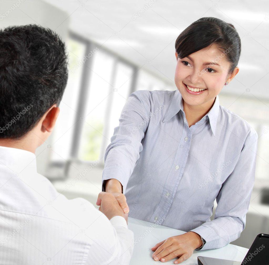 漂亮亚洲商务女人在她的办公室与人握手– 图库图片