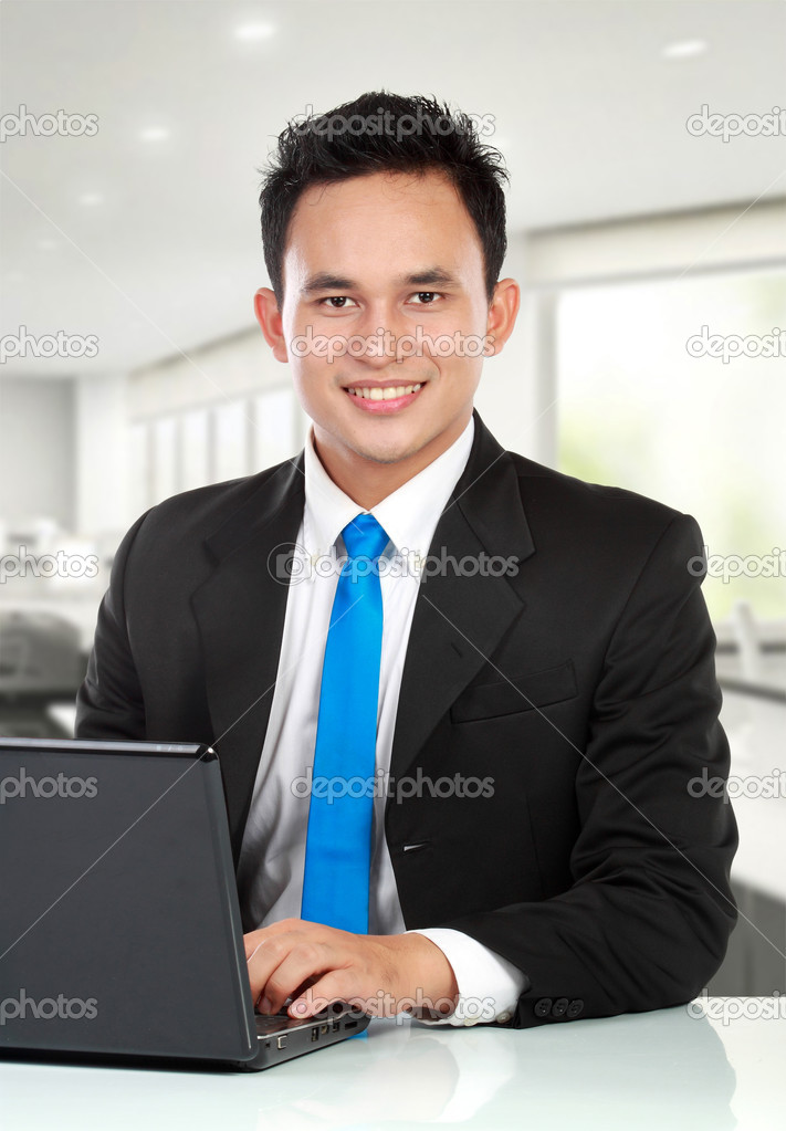 Portrait of a handsome young business man with a laptop working in the office — Stock Photo #11244986