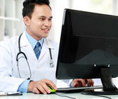 Doctor at his desk in front of computer — Stock Photo