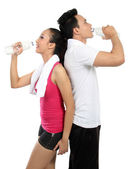 Man and woman drinking water after fitness — Stock Photo