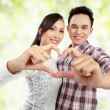 Royalty-Free Stock Photo: Young couple showing heart with fingers