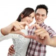 Young couple in love showing heart with fingers — Stock Photo