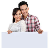 Couple holding blank banner on white — Stock Photo