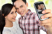 Young couple taking self portrait — Stock Photo