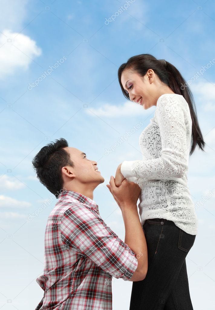 Young man romantically proposing to girlfriend under the blue sky — Stock Photo #11410352