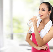 Attractive asian smiling woman drinking water — Stock Photo
