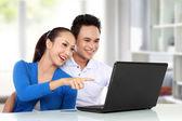улыбаясь пара с помощью ноутбука — Стоковое фото