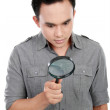 Man looking through a magnifying glass — Stock Photo