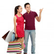 Couple with shopping bags pointing — Stock Photo #11501113