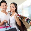 Attractive happy couple carrying shopping bag — Stockfoto #11501123