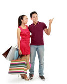 Couple with shopping bags pointing — Stock Photo
