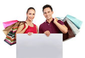 Shopping couple with blank board — Stock Photo
