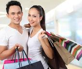 Atrakcyjny szczęśliwa para, noszenie torby na zakupy — Zdjęcie stockowe