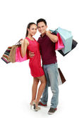 Attractive happy couple carrying shopping bag — Stock Photo