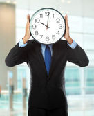 Man covering his face with clock — Stock Photo