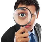 Businessman with magnifying glass — Stock Photo