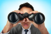 Business man looking through binocular — Stok fotoğraf