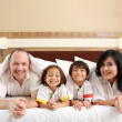Happy family on white bed - Stock Photo