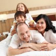 Royalty-Free Stock Photo: Happy family on white bed