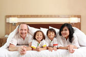 Happy family on white bed — Stock Photo