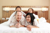 Happy family in the bed — Stock Photo
