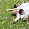 Family lying down in the park — Stock Photo #11904511