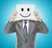 Businessman with smiling mask — Stock Photo