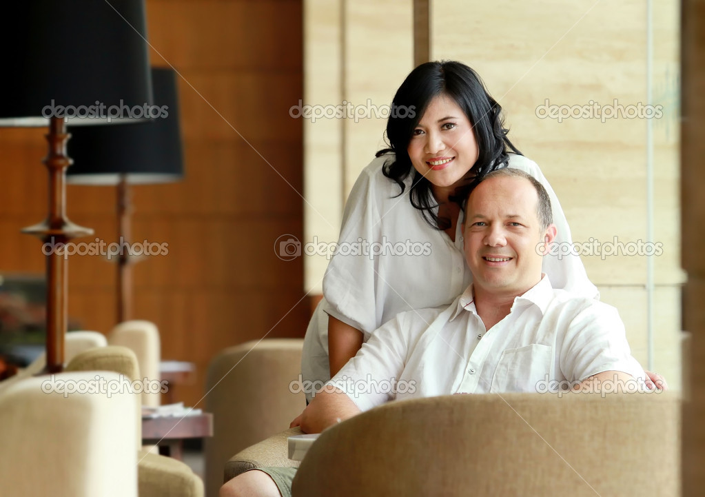 Couple looking at the camera while sitting on the sofa  Stock Photo #11917110