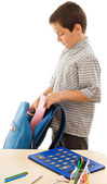 Schoolboy putting an exercise book in the schoolbag — Stock Photo