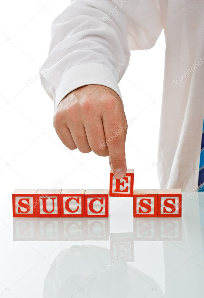 Businessman putting E block to complete the SUCCESS sign - isolated — Foto Stock #10861330