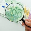 Banknotes and magnifying glass — Stock Photo