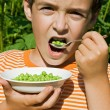 Photo: Boy eating peas