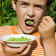 Boy eating peas — Stock Photo