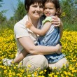 Mother and her daughter sitting among yellow flowers — Stock Photo