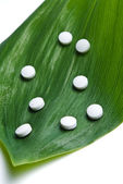 Leaf with white pills — Stock Photo