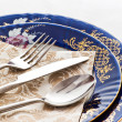 Silverware on fine porcelain — Stock Photo