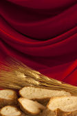 Bread Slices with Wheat on Red Satin — Stock Photo