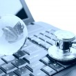 Stethoscope and globe on a laptop keyboard — Stock Photo
