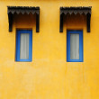 Blue window on yellow grunge wall — Stock Photo