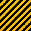 yellow and black diagonal hazard stripes painted on old brick wa — Stock Photo