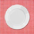 White plate on red and white tablecloth — Stock Photo