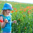 Young blond girl with red flowers — Stock Photo