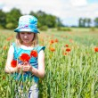 Young blond girl with red flowers — Stock Photo #11096250