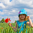 Young blond girl with red flowers — Stock Photo #11096356