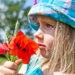 Young blond girl with red flowers — Stock Photo #11096478